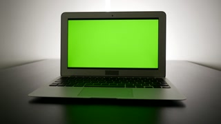 isolated green screen on laptop computer display. modern office desk table view