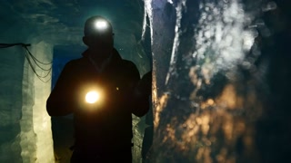 male explorer discovering ice inside glacier cave tunnel holding flashlight