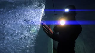 male scientist exploring ice glacier using a flashlight. blue light beam