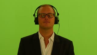 man listening music with headphones. closed eyes. isolated green screen