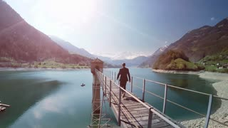 man walking over bridge in lake panorama scenery