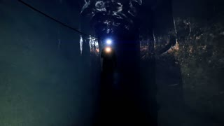 man walking through ice tunnel discovering glacier cave using a flashlight