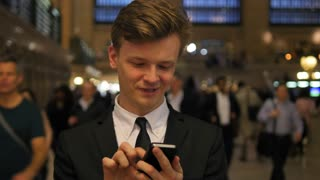 one young business man texting on smart phone in public station