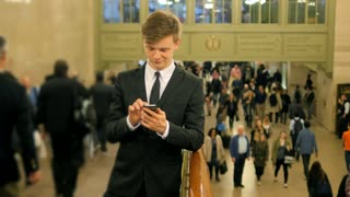 one young man standing in the crowd texting on smart phone surrounded by people