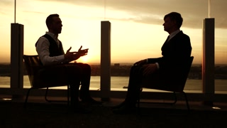 outdoors business meeting at sunset magic hour light. two man talking together