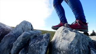 person hiking over rock mountain stones. close up of walking feet. nature adventure background
