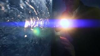 person using flashlight to discover ice glacier cave. mystical scene