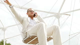 phone conversation of young caucasian businessman in white casual suit