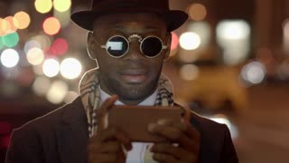 Portrait of black man using smart phone tablet in the city at night