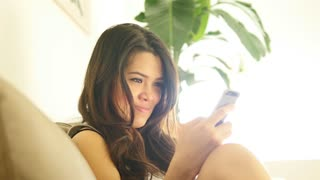 portrait of young asian women sitting on couch at home using smart phone