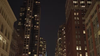 pov car view of city buildings at night