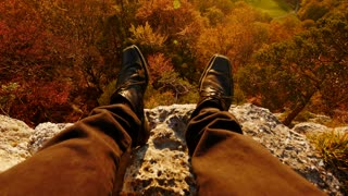 pov view of man sitting on stone rock overlooking autumn forest landscape