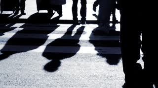 shadow silhouette of people walking through city. pedestrians background