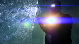 silhouette of male researcher discovering glacier cave holding flashlight