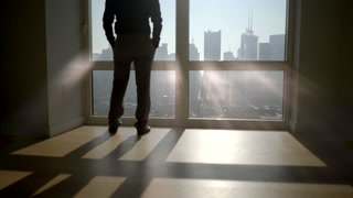 silhouette of man in modern office in the city standing on large window front