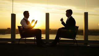 silhouette of people having a business meeting outdoors at sunset. smart phone