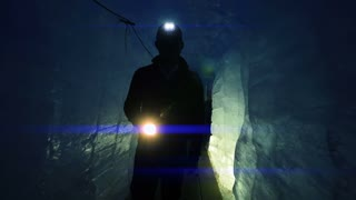 silhouette of scientist researcher discovering glacier cave holding flashlight