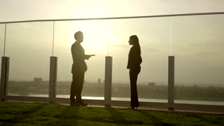 silhouette view of man talking to women on rooftop lounge