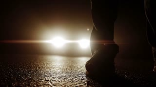 spooky darkness night scenery background. silhouette of one person walking in front of car lights