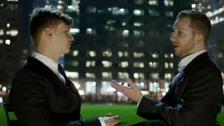 two businessman chatting together in the city at night. urban lifestyle people