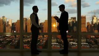 two businessman having a business meeting in modern high rise office building