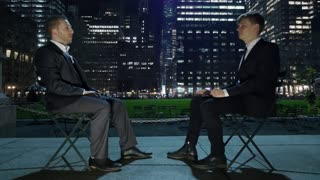 two male friends laughing having a funny conversation in city park at night