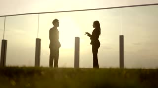 two young business people having a conversation on rooftop at sunset