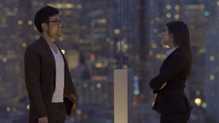 two young business people standing on rooftop building at night
