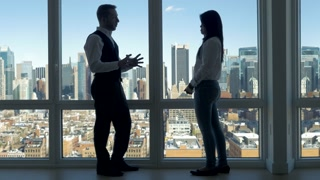 two young business professionals talking together in modern office building