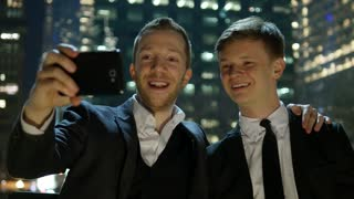 two young men watching something funny on smart phone outdoors at night