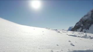 Person walking though deep snow in mountain range environment