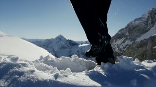 Slow motion shot of person hiking in snow covered alpine landscape