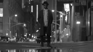 water reflection of black man standing on street in the city at night