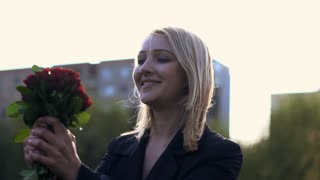 woman spinning around holding roses in her hands shot in slow motion