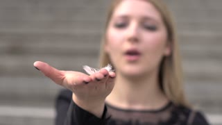 women hand blowing white feather slow motion