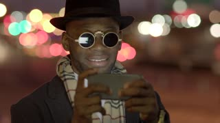 young black man in bad boy look using smart phone in the city at night