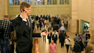 young business man commuter talking on the phone in crowded train station