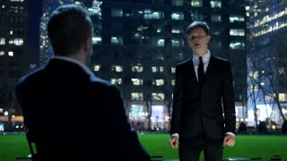 young business man talking to client in city park at night. people meeting