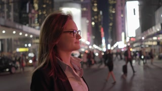 Young business women using smart phone while walking in the city at night