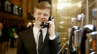 young businessman talking in the phone booth telling success story. happy person