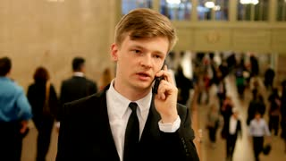 young businessman talking on the phone in crowded train station hall