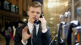 young caucasian business man talking in phone booth in train station