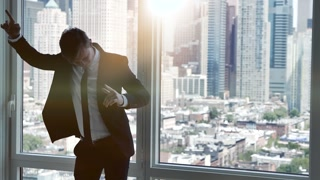young caucasian businessman dancing in modern office. lifestyle background