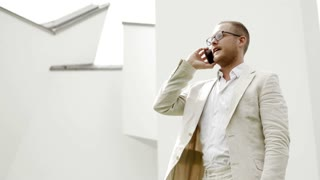 young caucasian businessman talking on the phone outdoors. white casual suit