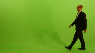 young caucasian businessman walking across frame against green screen background