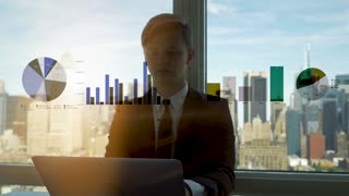 young caucasian businessman working in modern office. city skyline background