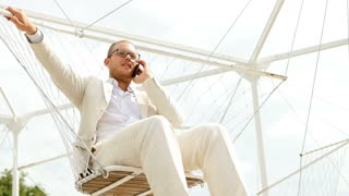 young caucasian man wearing casual white suit talking on the phone outdoors