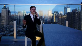 young man having a phone conversation on rooftop bar. city skyline background