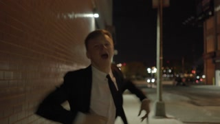 young man walking down the street dancing like crazy. successful businessman