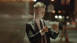 young successful businessman using tablet computer outdoors in the city at night